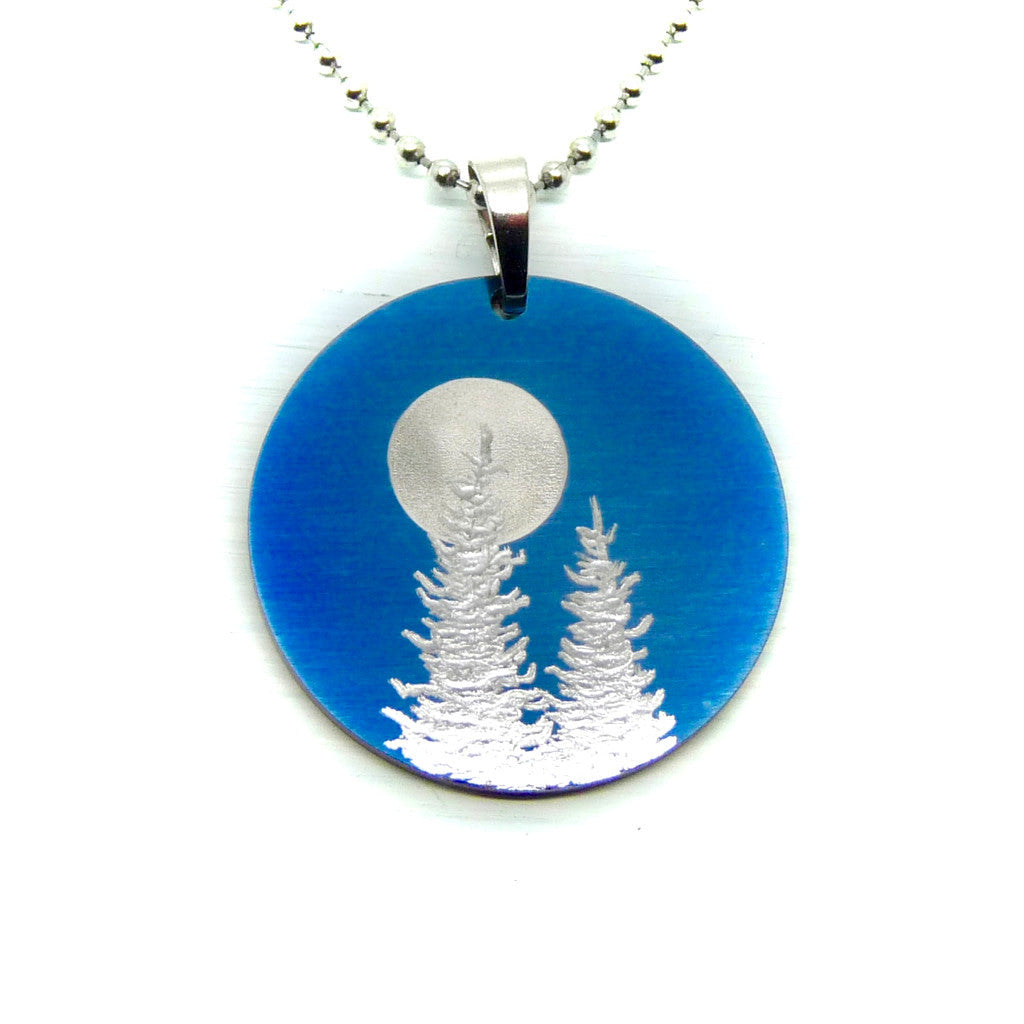 Midnight blue round necklace with two trees and a full moon.
