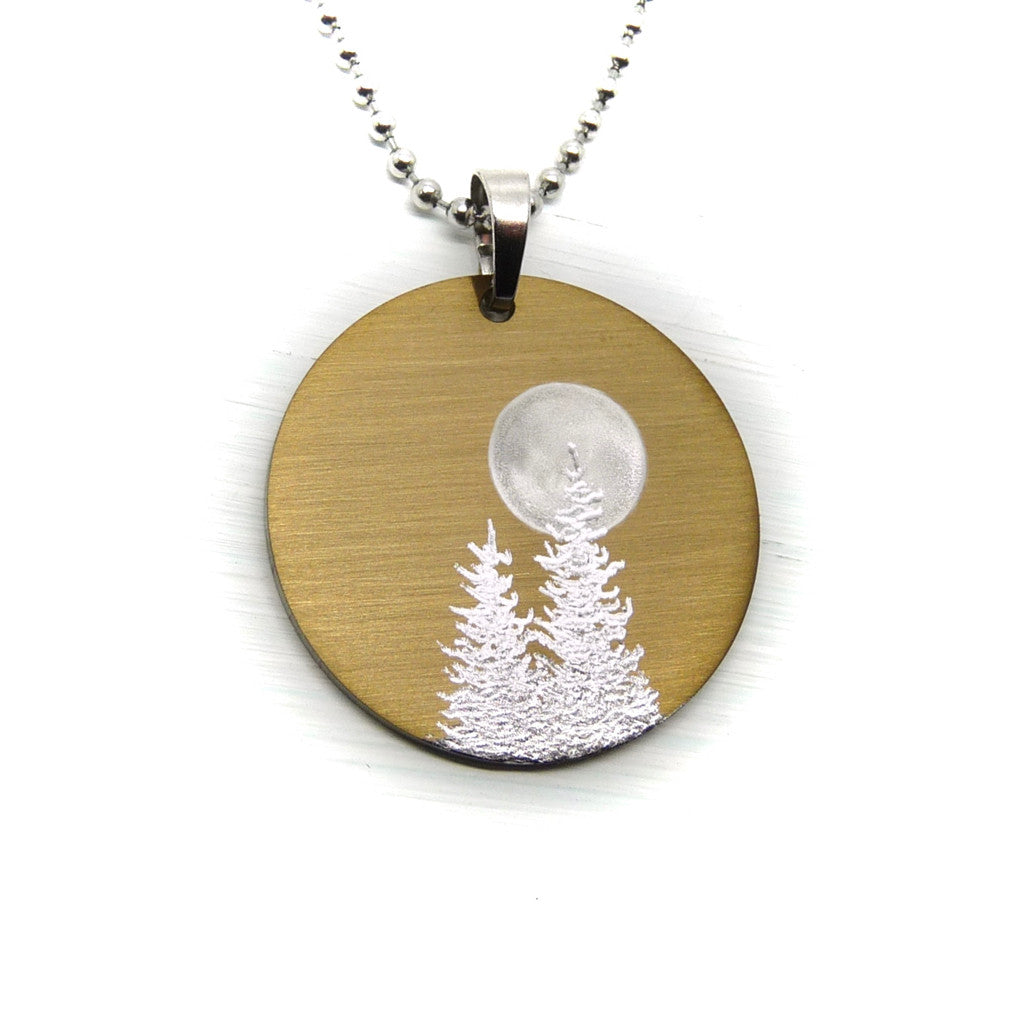 Gold circle necklace with two silver trees and full moon.