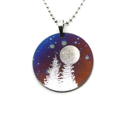 round cosmic sky necklace with two trees and a full moon.