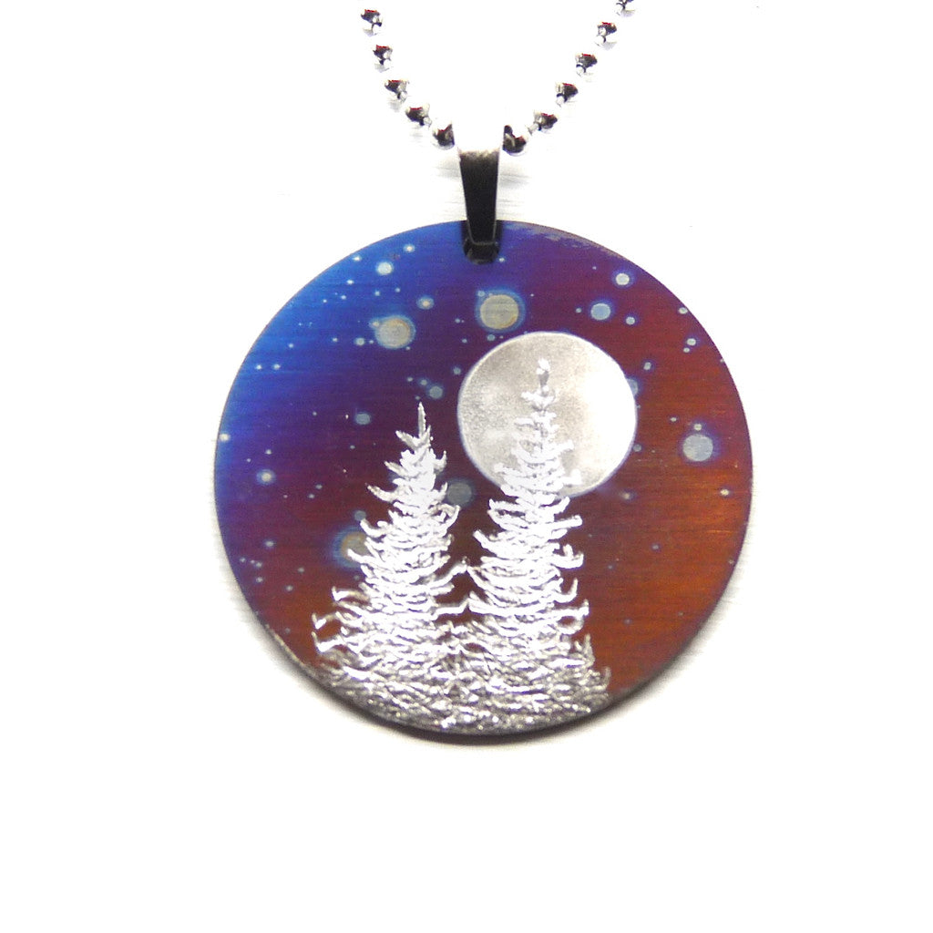 Round necklace with cosmic sky, two trees and a full moon.