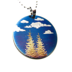 Two gold trees and cloudy blue sky round pendant.