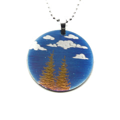 Circle pendant with blue sky, clouds and gold trees.
