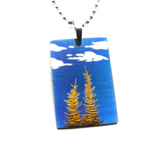 Gold trees, blue sky and clouds on rectangle pendant.