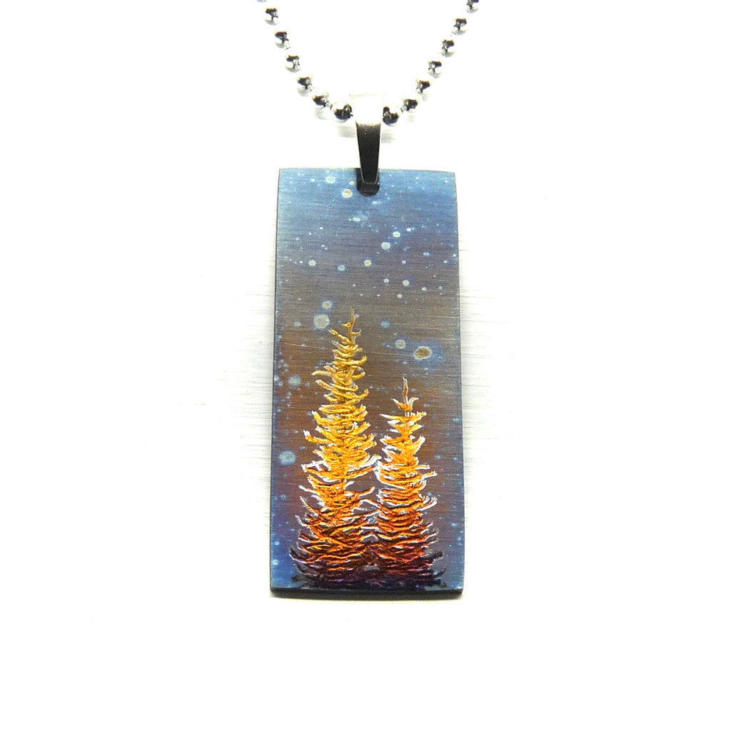 Rectangle necklace withgold trees and cosmic night sky.