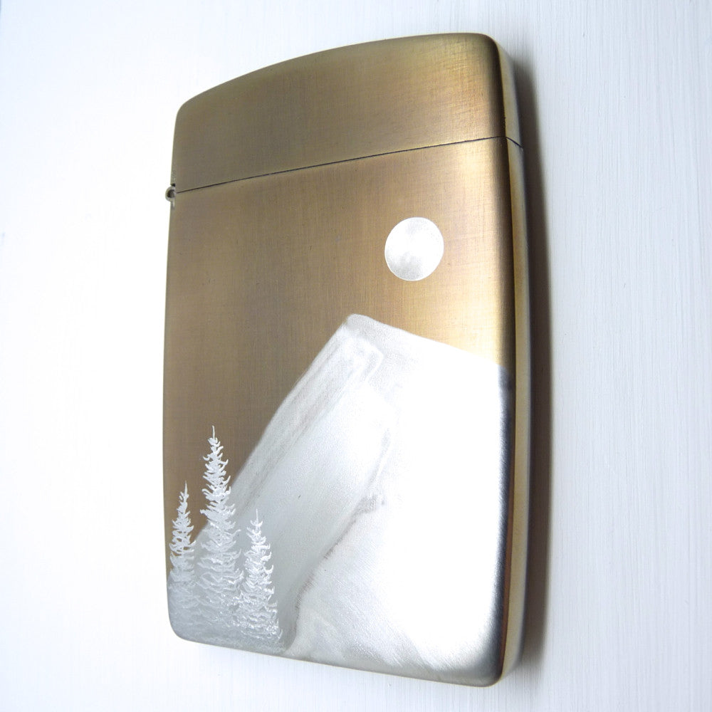 gold card case with silver mountain, moon and trees