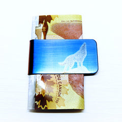 Howling wolf silhouette on a blue money clip. With cash.