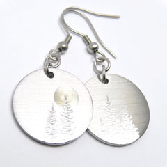Round earrings with silver trees and a gold moon.