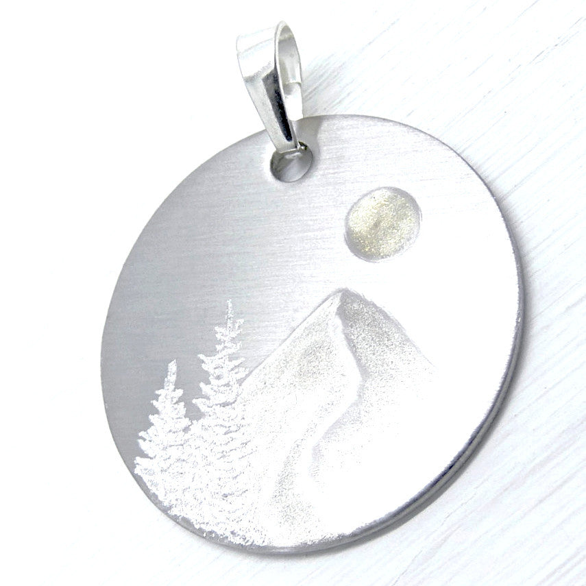 Silver mountain scene on circle necklace.