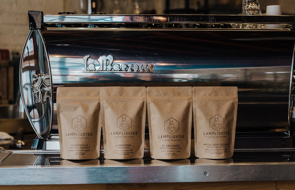 Four 4 ounce bags of coffee in front of our La Marzocco espresso machine