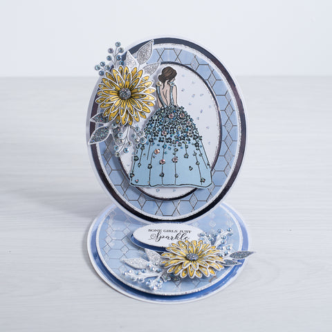 A beautiful layered oval card with blue and white card and a sparking geometric glitter background. The card features a sparkling yellow 3D flower with glitter foliage and a lady wearing a blue dress adorned with crystals.