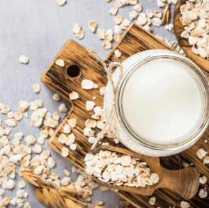 Picture of a glass jar with milk on a wooden tray and oat sprayed around