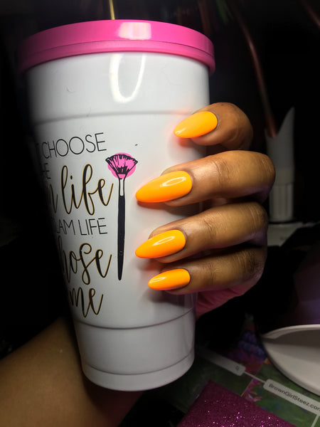 "brown hand wearing bright yellow-orange petite almond shaped nails. Holding a white drinking cup that says ""I didn't choose the glam life, the glam life chose me"""