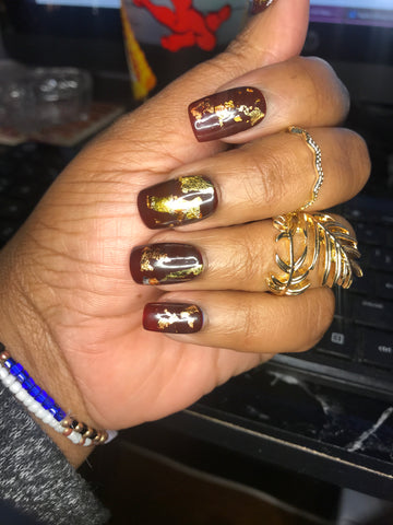 Brown hand model, wearing short square, burgundy nails with gold leaf on top.