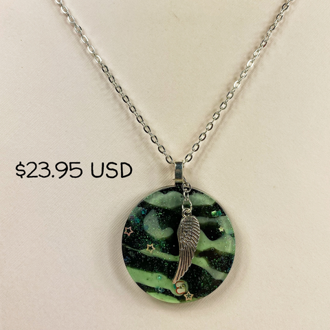 "A necklace on a silver chain.  The pendant is a 2"" flat circle with swirled green and black resin, and there is a 1.5"" silver feather hanging in front of this."
