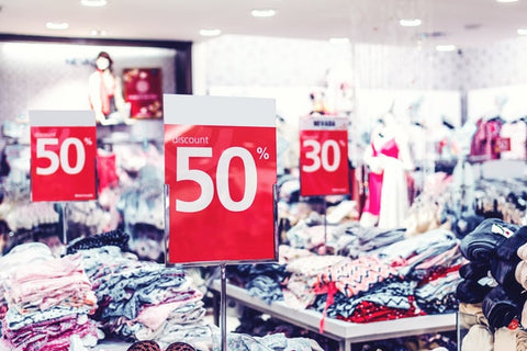 Interior of brightly lit store with many tables loaded with folded clothing, all sporting 50% off signs