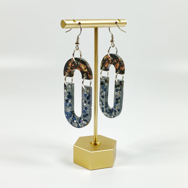 Double Dangle Brown and Black Starry Resin Hoop Earrings on brass display stand