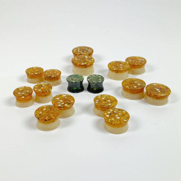 Golden Stars and Glitter over Opalescent Mica Resin Gauges Plugs various sizes arranged in a starburst pattern