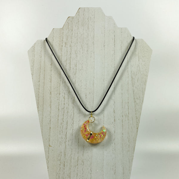 Gold Banded Blush Sparkly Crescent Moon Resin Pendant Necklace on pale wood display stand