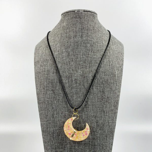 Gold Banded Blush Sparkly Crescent Moon Resin Pendant Necklace on grey tweed necklace stand