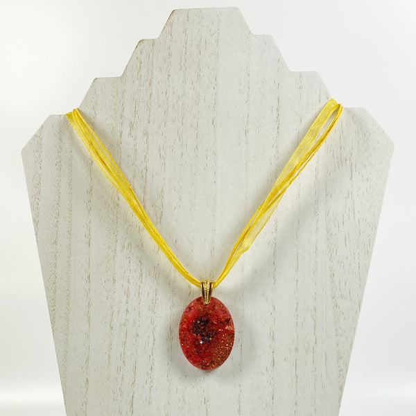 Red and Gold Oval Resin Pendent Necklace on pale wood display stand