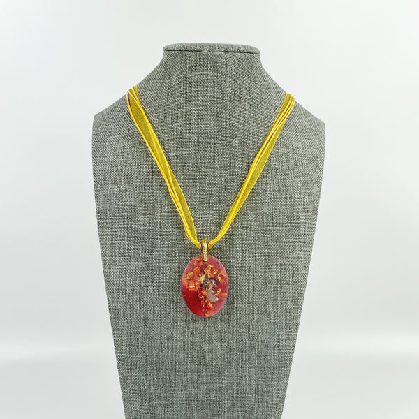 Red and Gold Oval Resin Pendent Necklace on grey tweed necklace display stand