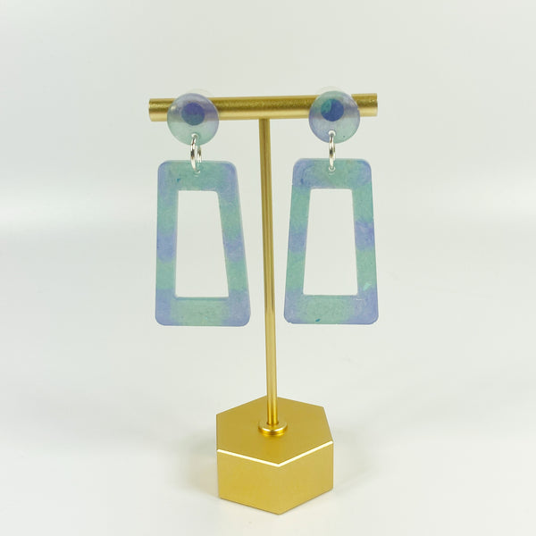 Blue and Purple Square Hoop Resin Dangle Earrings on brass display stand