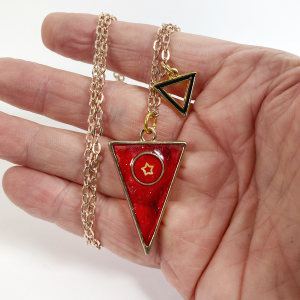 Scarlet Triangle with a Star Resin Necklace held in hand for size reference