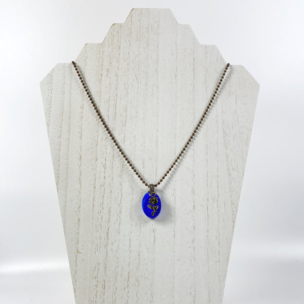 Deep Midnight Blue Resin Necklace with Bronze Rose on pale wood display stand