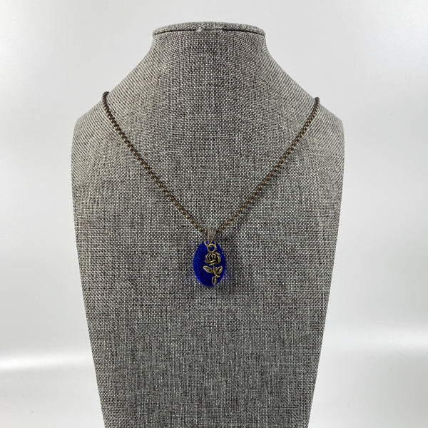 Deep Midnight Blue Resin Necklace with Bronze Rose on grey tweed necklace display stand