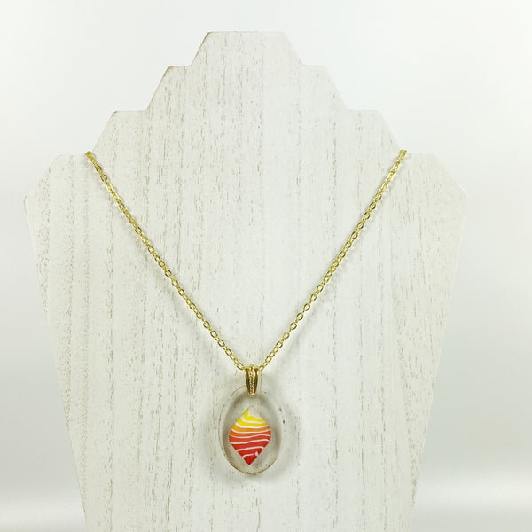 Stacked Bright Polymer Clay in Clear Resin Handmade Pendent Necklace on pale wood necklace stand