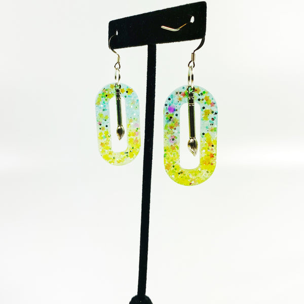 Northern Lights Oval Hoop Resin Earrings with Paint Brush Charm on black earring stand