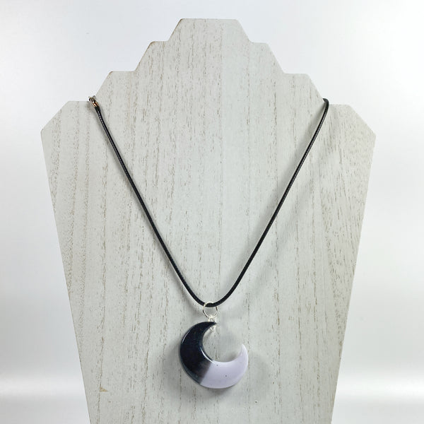 Crescent Moon Eclipse Resin Necklace on pale wood necklace display stand