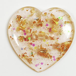 Gold flakes in blush resin heart button, front view