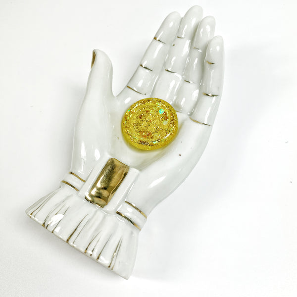 Marigold Rimmed Resin Button, shown in display hand