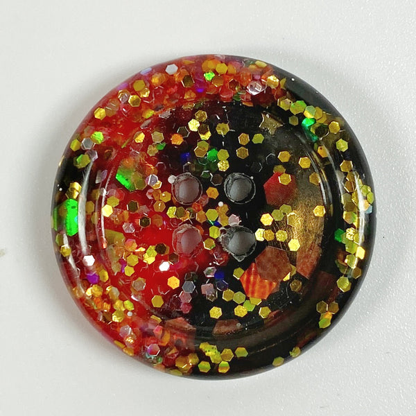Red & Black rimmed resin button with gold glitter, front view