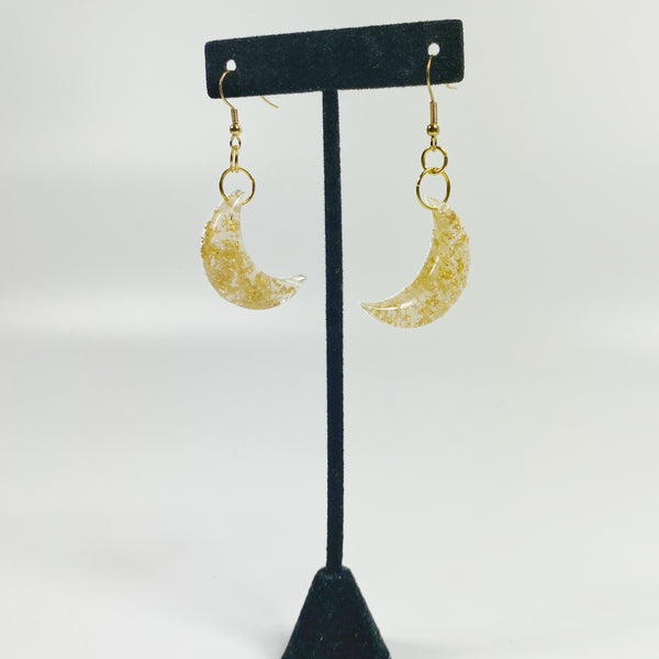 Pale Crescent Moon with Gold Flecks Resin Earrings on black earring stand
