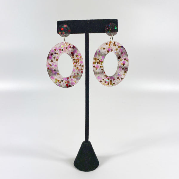 Inky Stars Brown and Blush Wide Resin Hoop Earrings on black earring stand