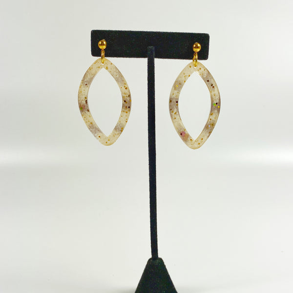 Tortoiseshell Brown and Blush Pointed Oval Hoop Resin Earrings on a black earring stand