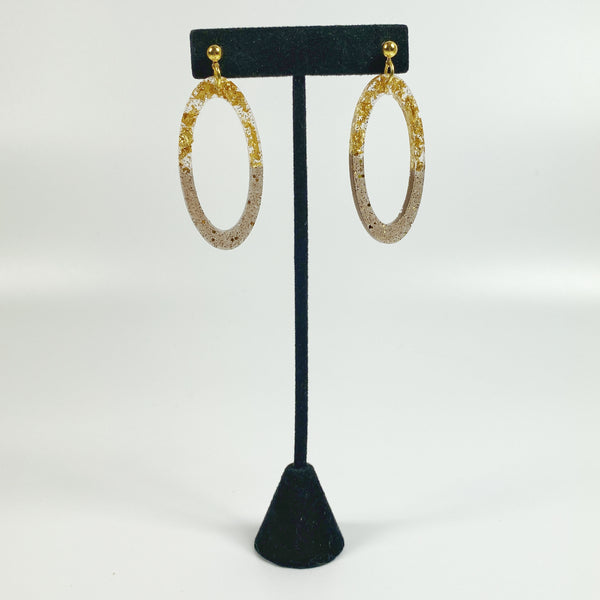 Gold Leaf & Pale Brown Sparkly Oval Hoop Resin Earrings hanging on black earring stand