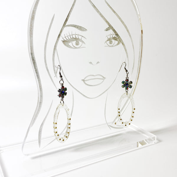 Clear resin oval hoop earrings with glitter and gold beads, colorful silver connector displayed on acrylic model head
