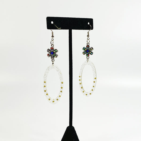 Clear resin oval hoop earrings with glitter and gold beads, colorful silver connector on black earring display stand