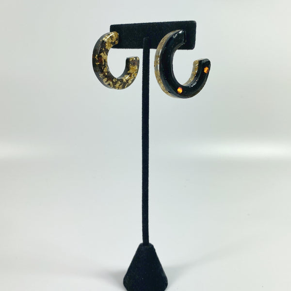 Gold Flakes over Coal C-Hoop Resin Earrings on a black earring stand.