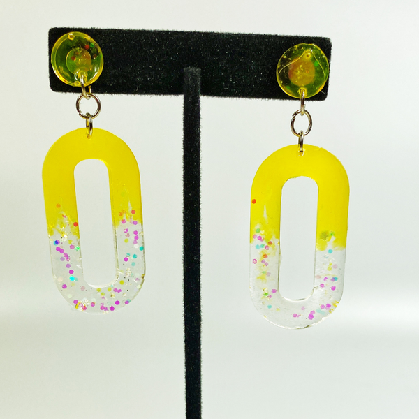 Sunrise earrings swinging on an earring display stand