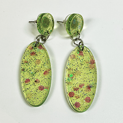 Oval earrings in pale green resin with plenty of sparkles