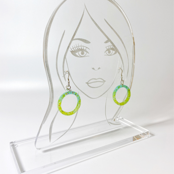 Green Hula Hoop earrings displayed on an acrylic face