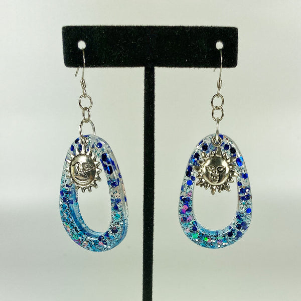 blue hoop earrings hanging on stand
