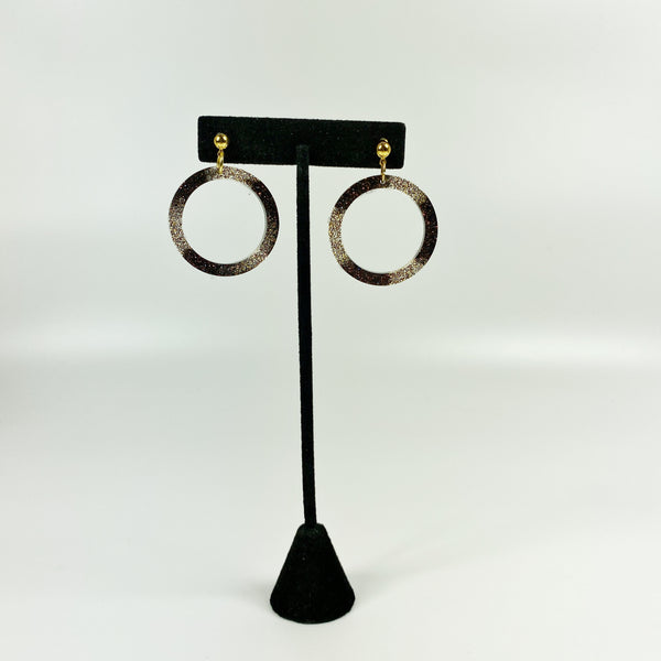 Gold and brown hoop earrings on earring stand