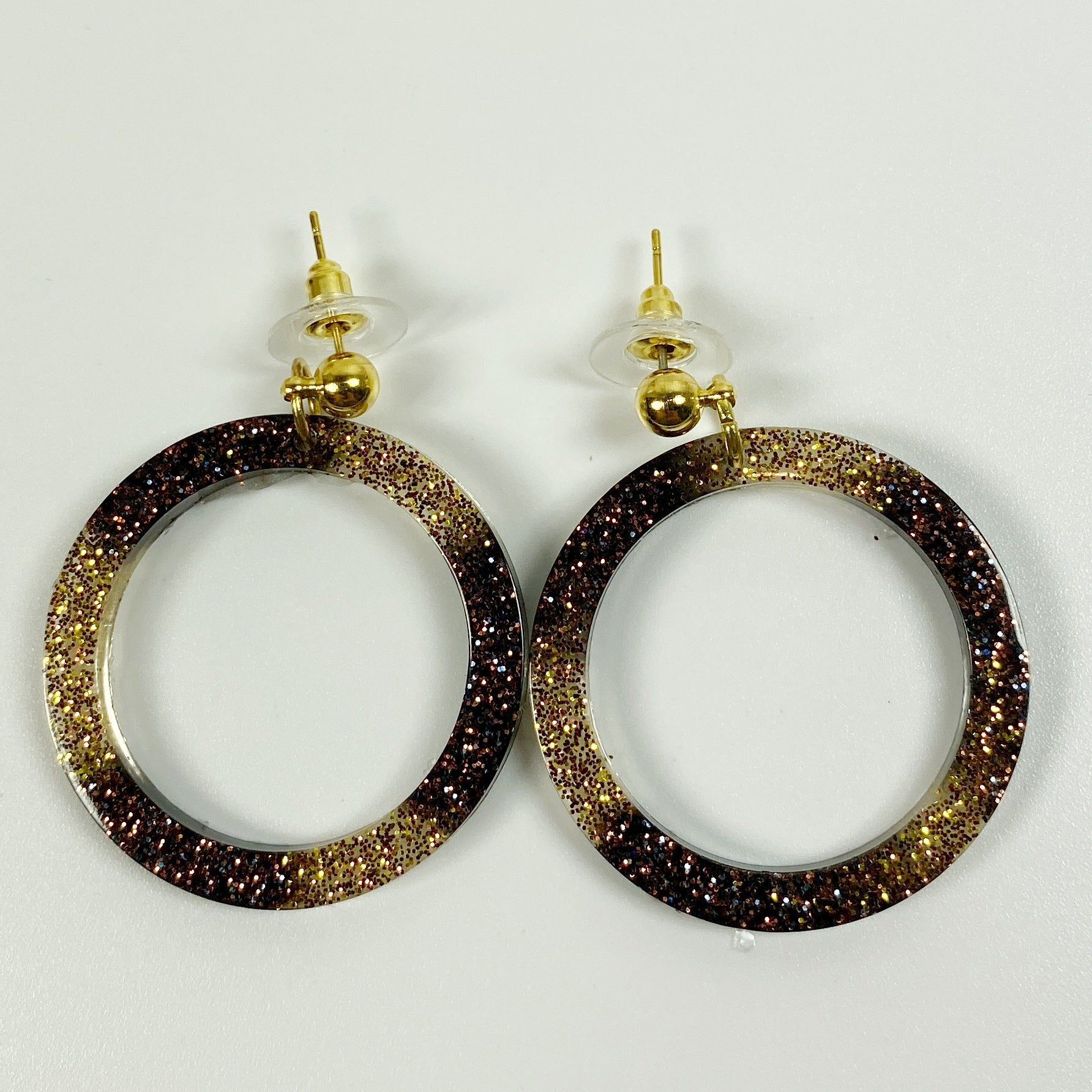 Hoop earrings of alternating gold and brown sparkly resin