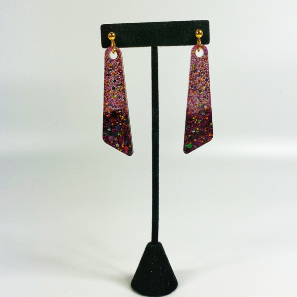 Batwing earrings shown on an earring stand
