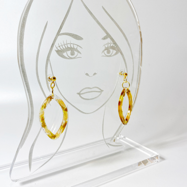 Tortoise shell pointed hoop earrings show on acrylic display head